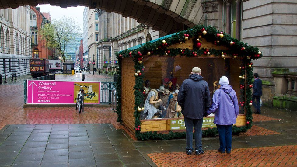 A couple looks at the nativity scene outside the council house