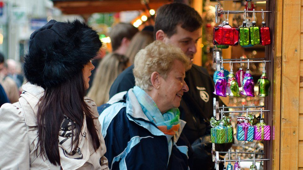 Customers browse a stall at the German market