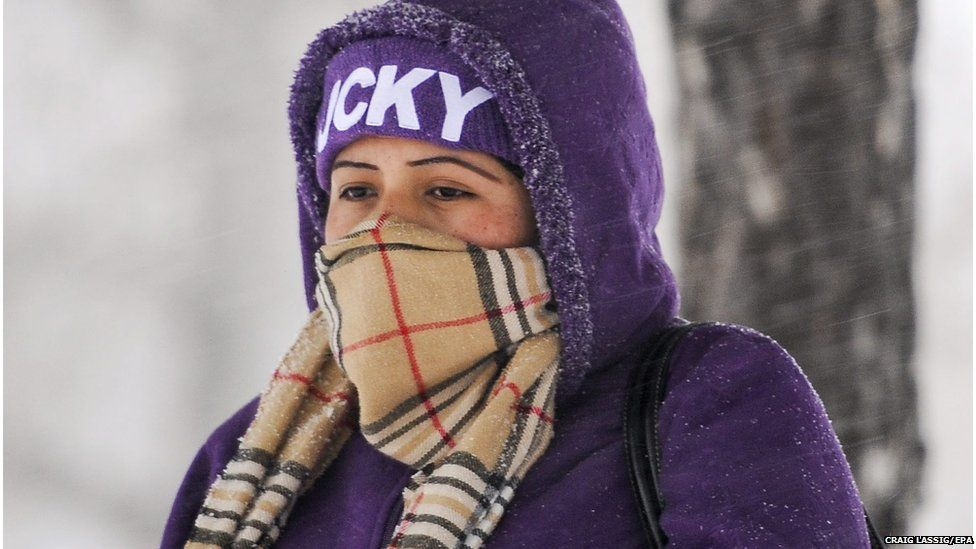 A woman wrapped up ahead of a snowstorm