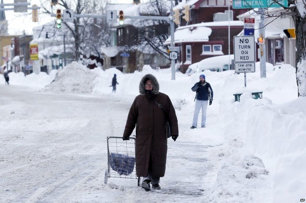 A woman walks down a snow-covered street in Buffalo, US