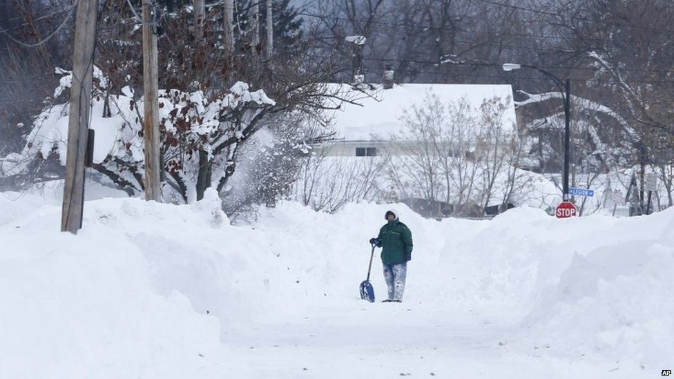 A man takes a break from shovelling snow in Buffalo, US