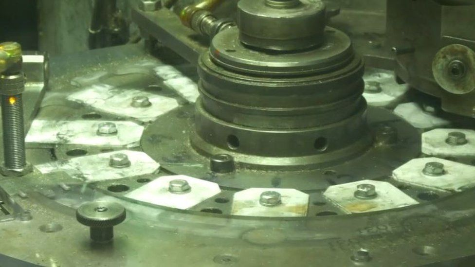 Y peiriant yn rhoi ei stamp ar yr arian // The machine stamping the coins