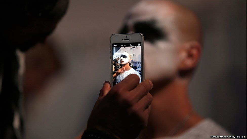 A model is pictured with a mobile phone during Lisbon Fashion Week