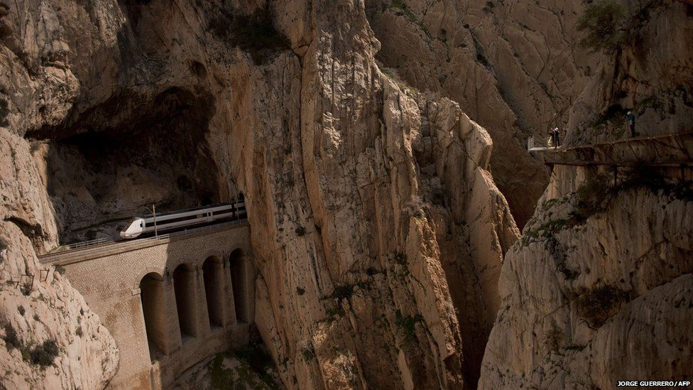 A train passes through a tunnel in the rocks as people walk on the El Caminito del Rey