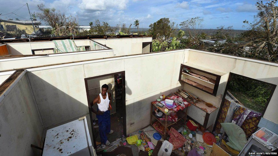 Uwen Garae stands in his home damaged by Cyclone Pam in Port Vila