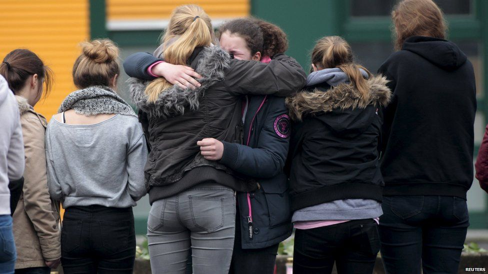 Students hug in front of the Joseph-Koenig-Gymnasium high school in Haltern am See