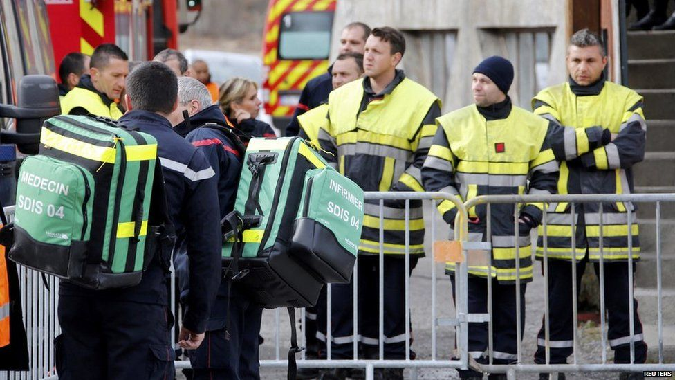 French firefighters gather outside the gymnasium where relatives and officials are due to pay tribute to the victims of the Airbus A320 crash in Seyne-les-Alpes
