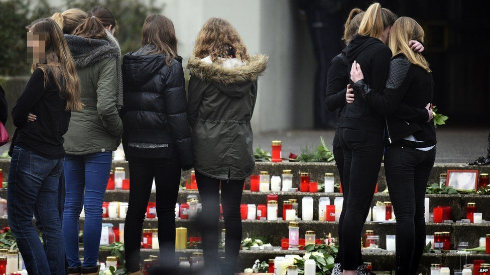 Students gather at a memorial of flowers and candles in front of the Joseph-Koenig-Gymnasium secondary school