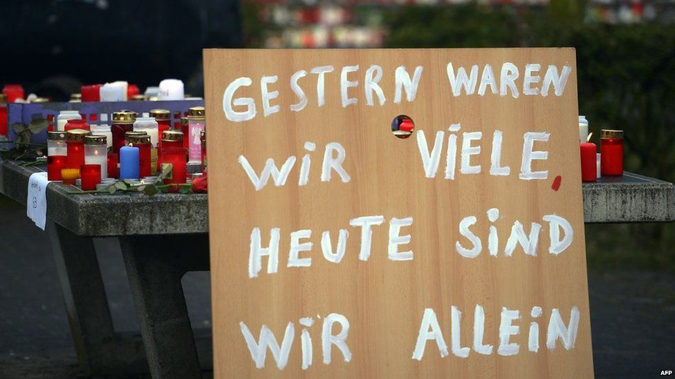 """A poster reading """"Yesterday we were many, today we are alone"""" can be seen in front of a memorial of flowers and candles near the Joseph-Koenig-Gymnasium secondary school in Haltern am See, western Germany"""