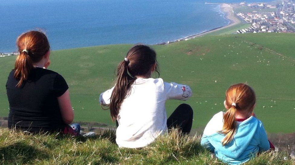 Girls sitting on top of a hill