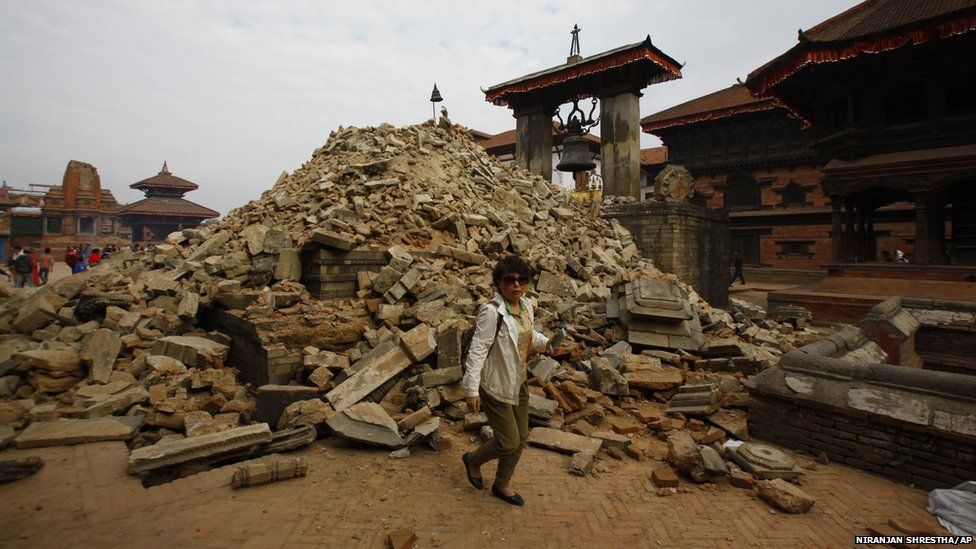 A Nepalese woman walks past a collapsed temple in Bhaktapur Durbar Square in Kathmandu (26 April 2015)