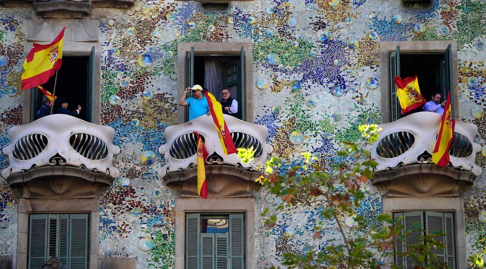 People wave Spanish flags from the Casa Batllo during a pro-unity demonstration in Barcelona on October 29, 2017