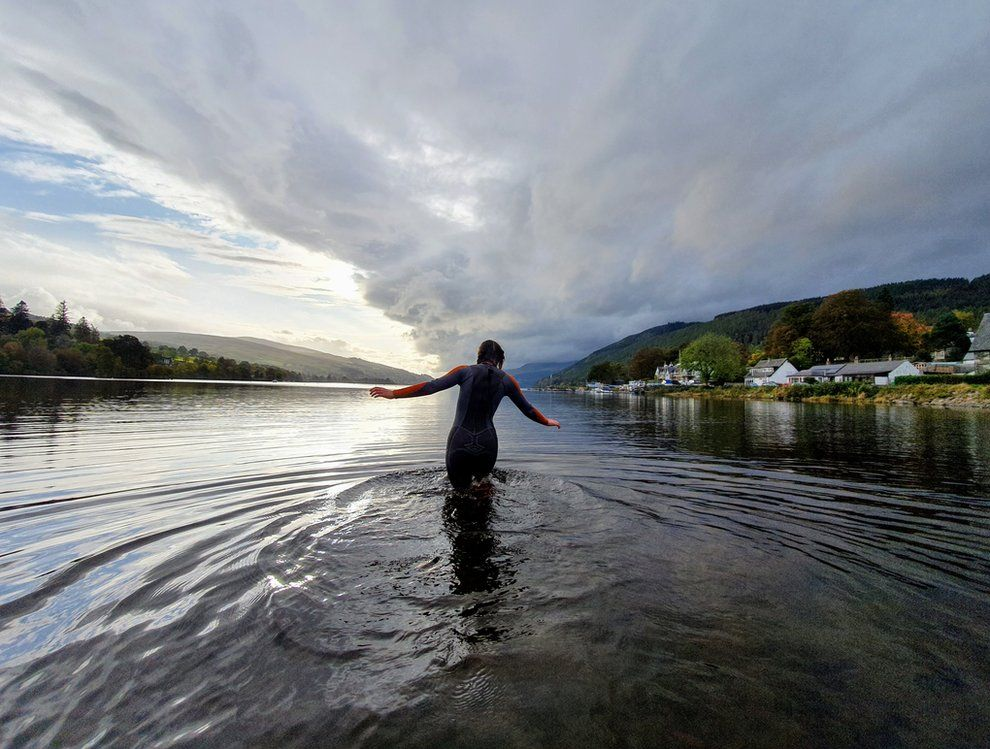 Woman wading into Loch Tay