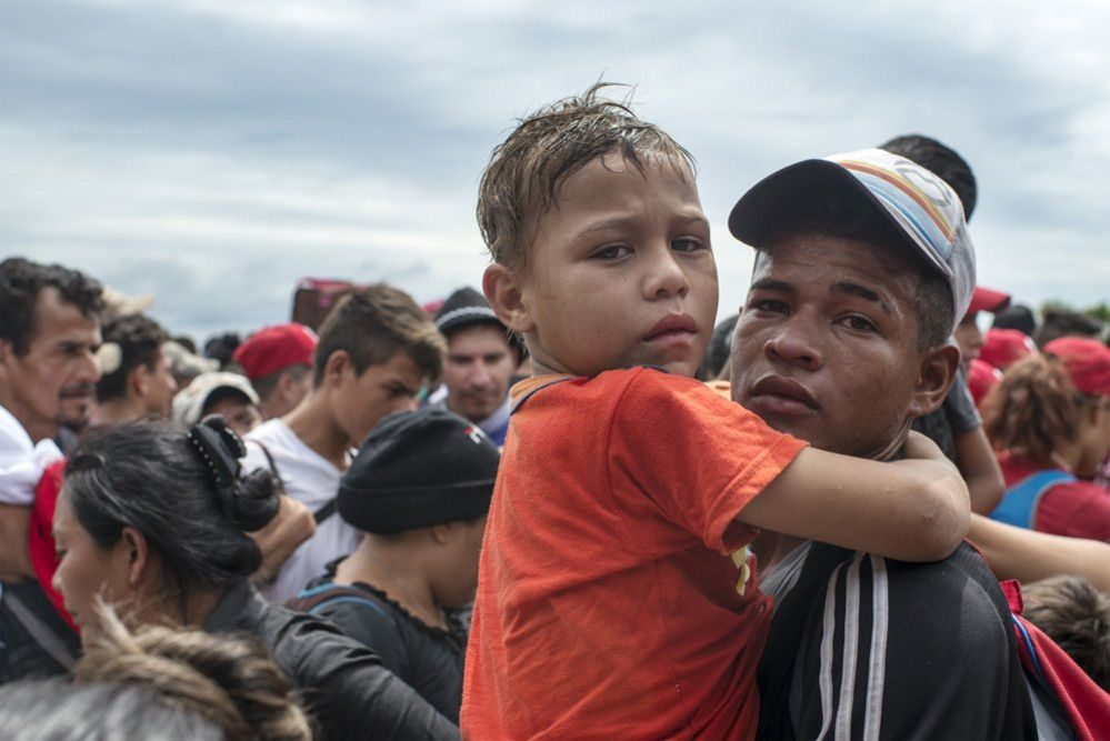 A man carries a child in his arms after the Mexican police fired tear gas>