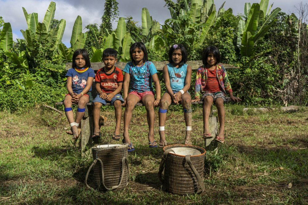 Children sit on a bench in the Waikas communituy