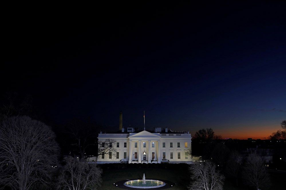 The sun sets near the White House on the final night of Donald Trump's presidency