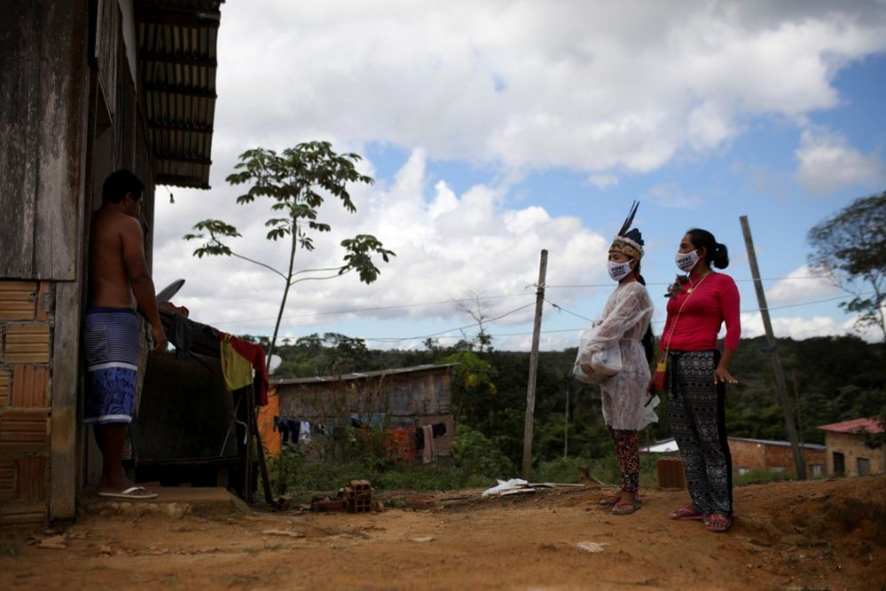Vanderlecia and Natalina wear protective masks as they talk to a neighbour outside of his home