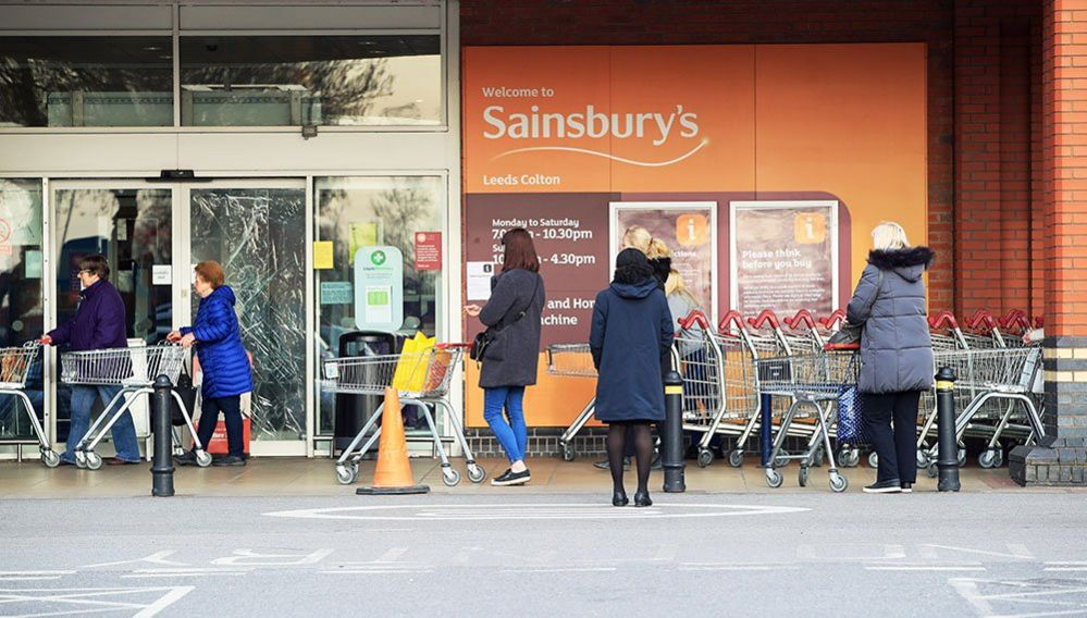 People observe social distancing while queuing at a Sainsbury's supermarket at Colton, on the outskirts of Leeds
