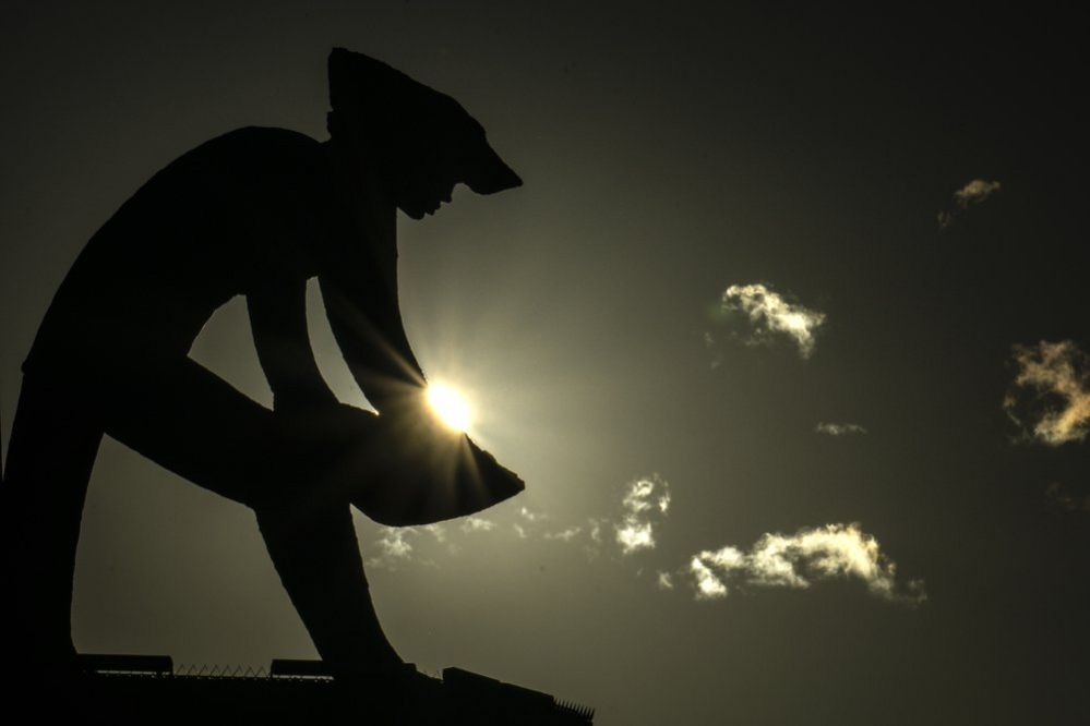 The silhouette of a miner is seen against the sun