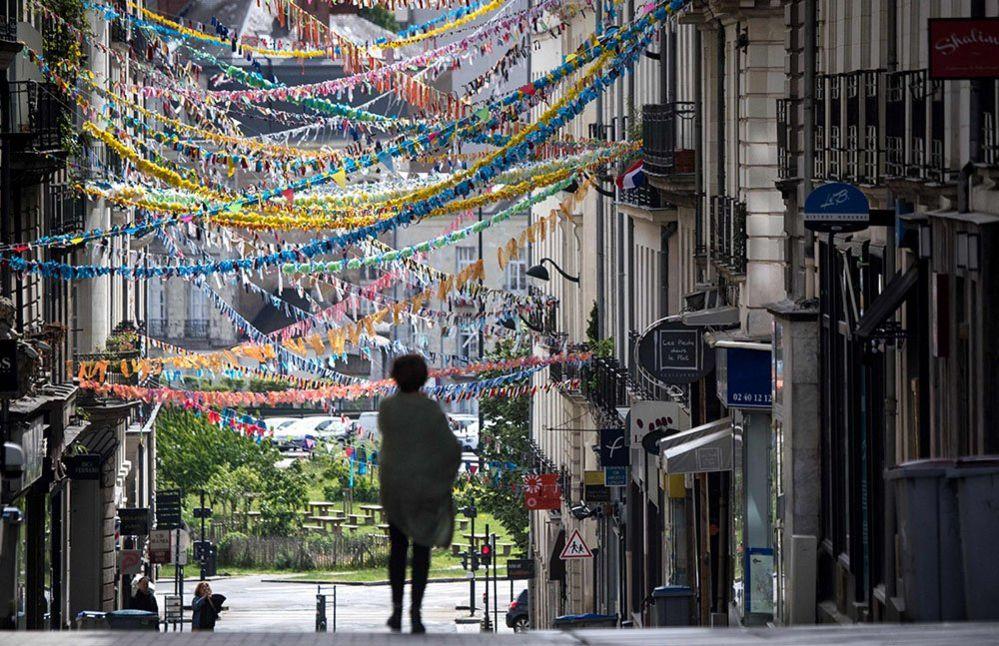 A woman walks down a street decorated by dozens of handmade garlands