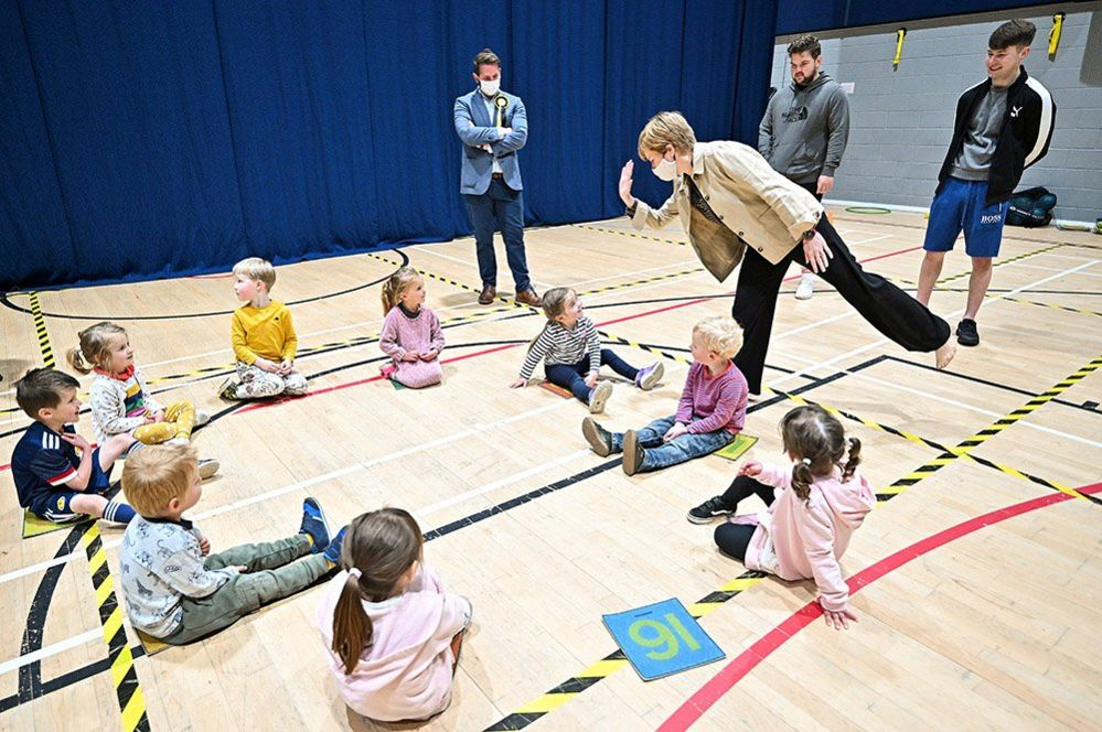 Scotland's First Minister and leader of the Scottish National Party, Nicola Sturgeon, plays with children