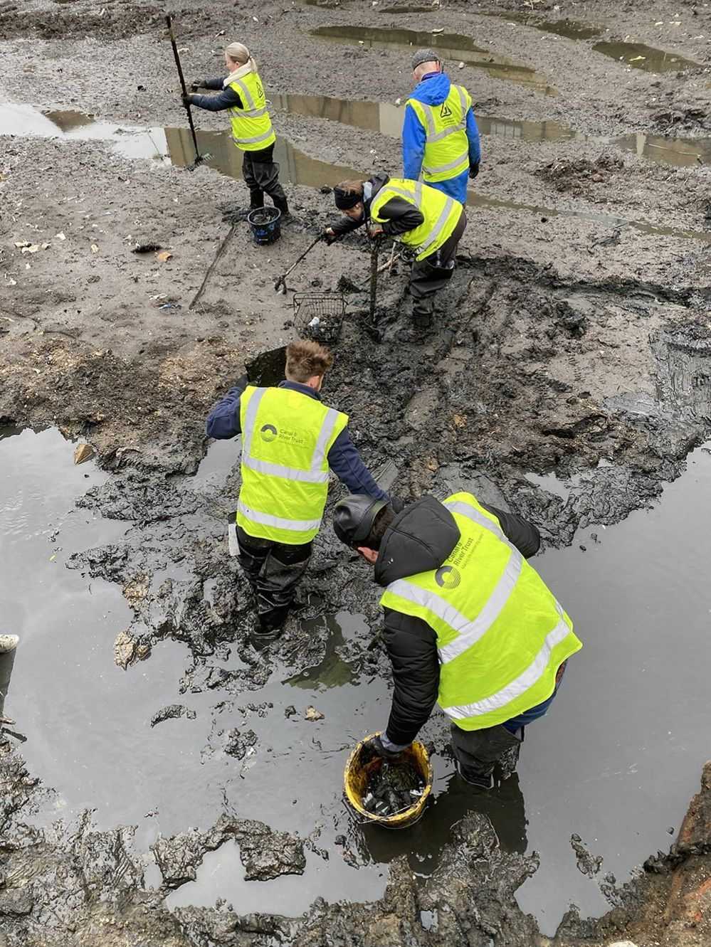 Volunteer litter-pickers brave the mud to gather rubbish from the canal bed