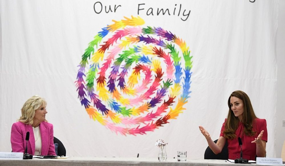 The First Lady sits socially distanced with the duchess, in front of a mural of multicoloured handprints