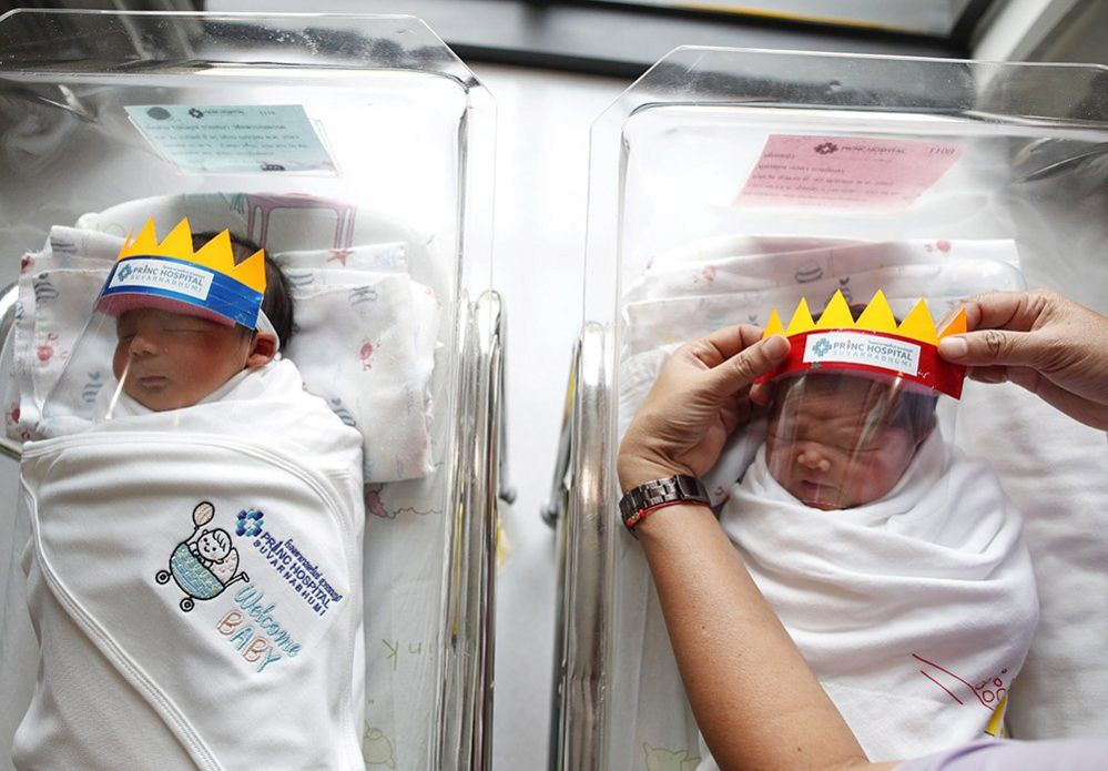 A nurse puts face shields on newborn babies at a hospital in Thailand