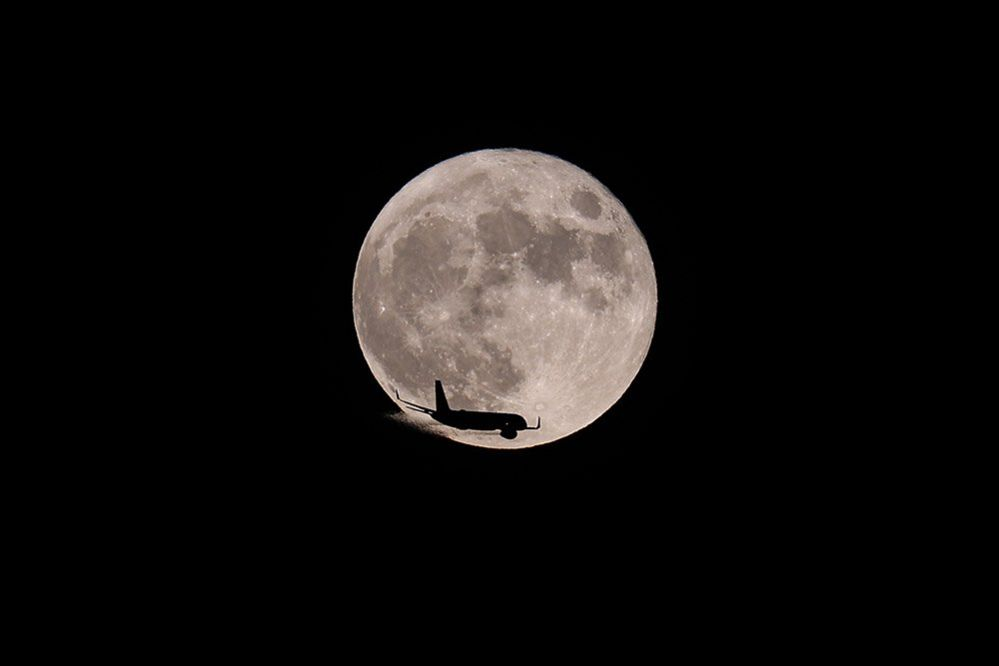 A plane passes in front of the moon