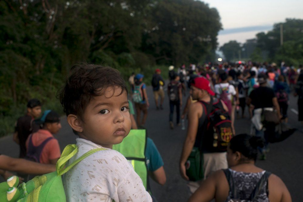A father carries his child on his shoulders as he walks on a road towards the Mexican city of Tapachula