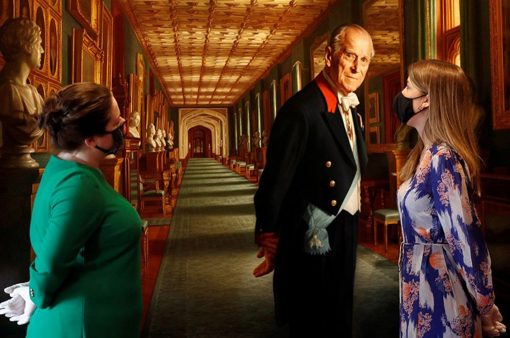 Members of the Royal Collection Trust staff pose for a photograph with a portrait of the Duke of Edinburgh