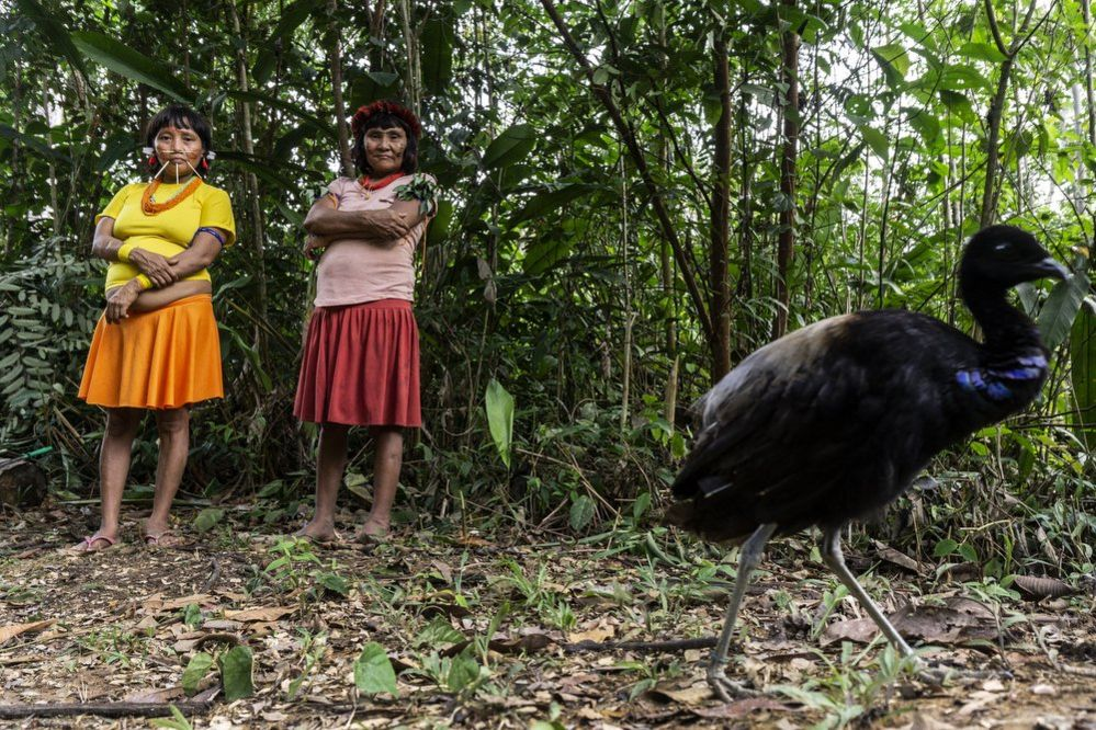 Two women pose for the camara in the Waikas community