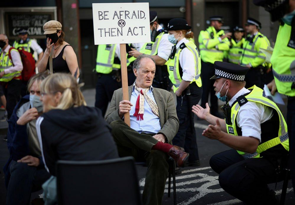 A police officer asks a demonstrator to leave during a protest of Extinction Rebellion activists