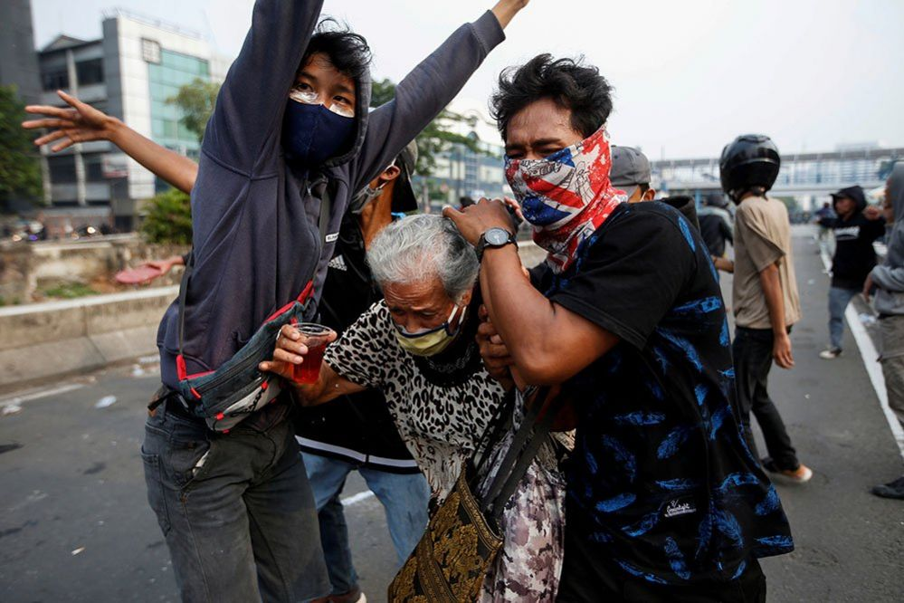 Demonstrators in Jakarta cover an elderly woman during clashes with police