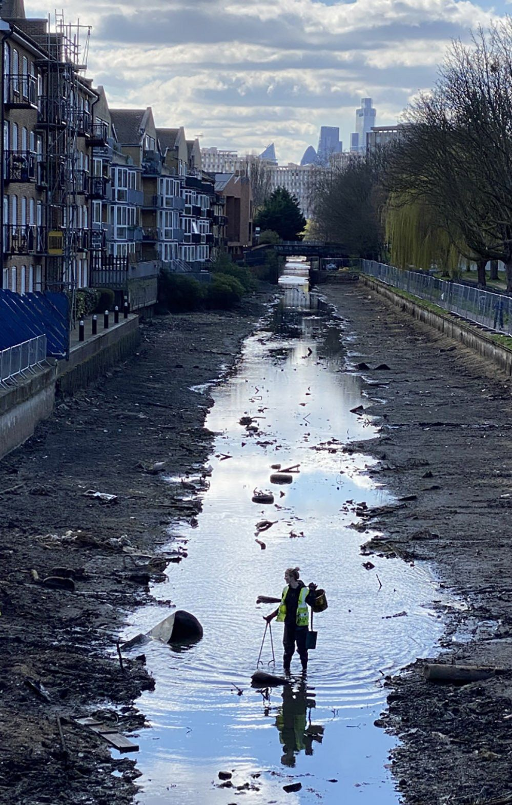 A volunteer litter-picker removes rubbish from the drained Hertford Union Canal