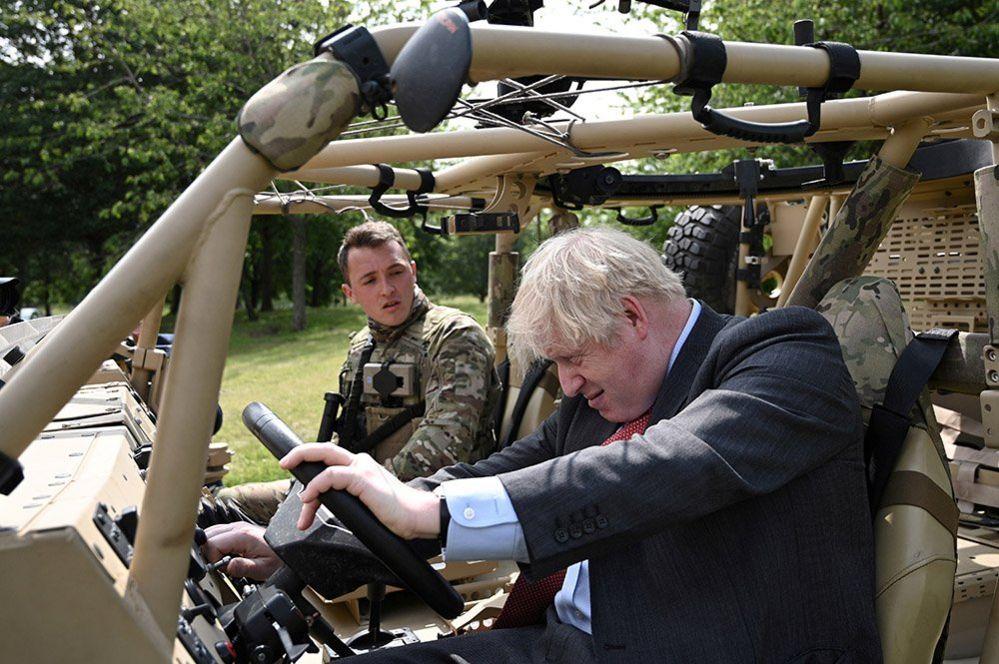 Boris Johnson poses in an armoured vehicle