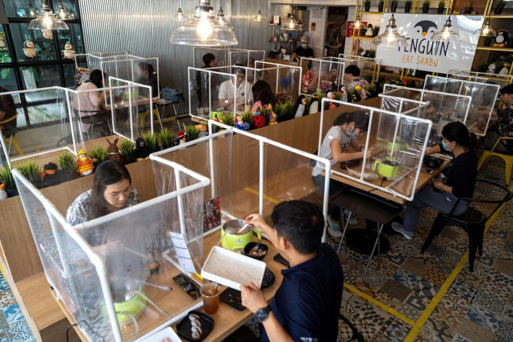 People eat in a restaurant with clear plastic barriers between diners