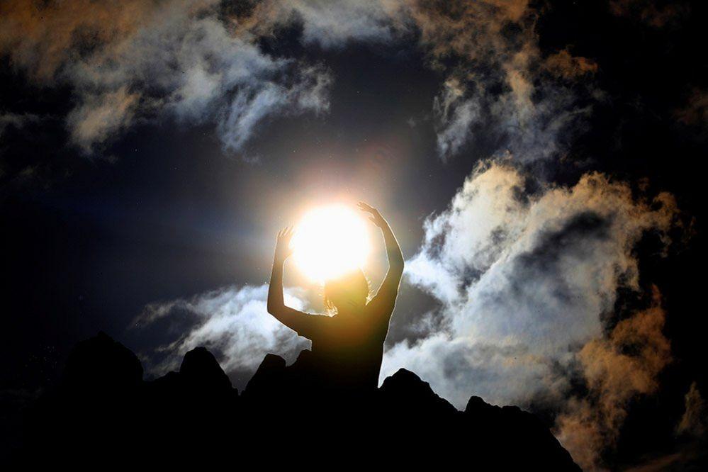 Arms raised around the Sun