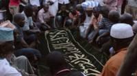 Des hommes priant lors de l'enterrement de Hafsa Mossi, ex-ministre assassinée à Bujumbura