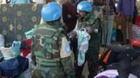 Des casques bleus s'occupant d'un bébé dans un camp de l'Onu à Juba, ayant accueilli des déplacés.