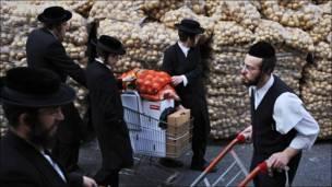 Judíos ultraortodoxos distribuyen papas para la pascua.