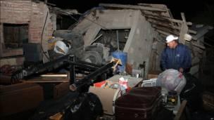 Un hombre rodeado de escombros y de objetos