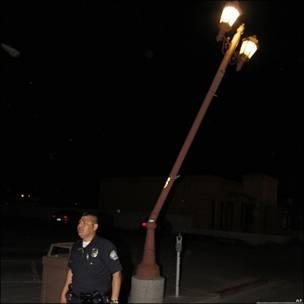 Un policía camina por el lado de un poste de luz que se dobló