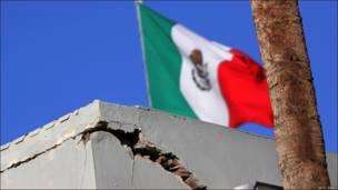 Bandera mexicana sobre edificio agrietado