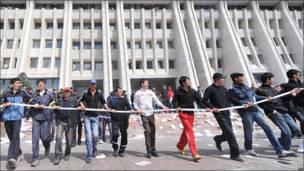 Добровольцы держат канат, чтобы удержать сторонников оппозиции вне здания