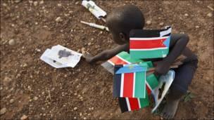 Niño recogiendo banderas en Sudán