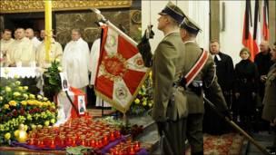 Soldados polacos saludan ante la bandera del ejército durante una misa especial dedicada a las víctimas del accidente en una catedral de Varsovia