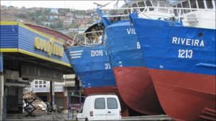 Barcos en frente de un establecimiento de Good Year de cambio de neumáticos