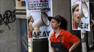 Una empleada de un restaurante de comida rápida delante de cárteles que llaman a la huelga en Grecia.