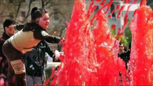 Una niña toca el agua roja de una fuente en el centro de Bucarest (Rumanía)